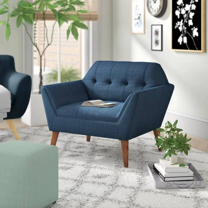 The tufted armchair in blue with wooden legs