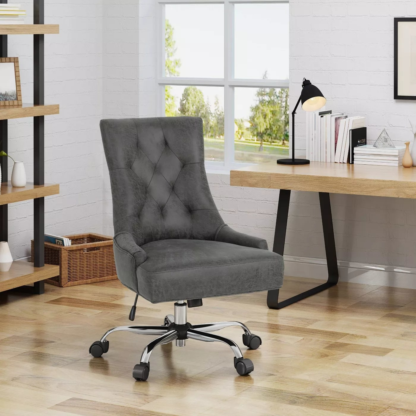 A gray, tufted, swivel chair