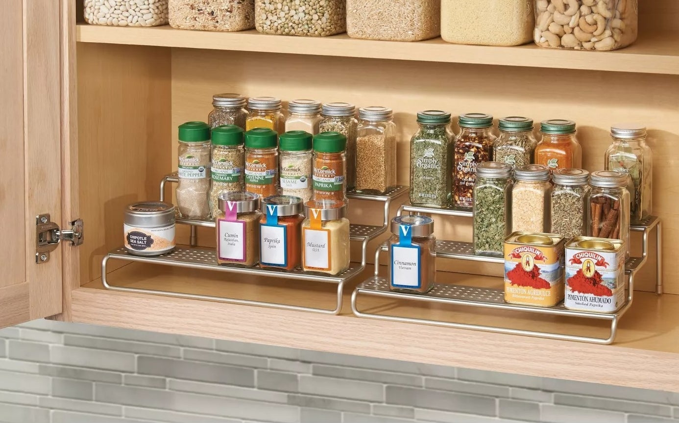 The spice rack filled with spices in a kitchen cabinet