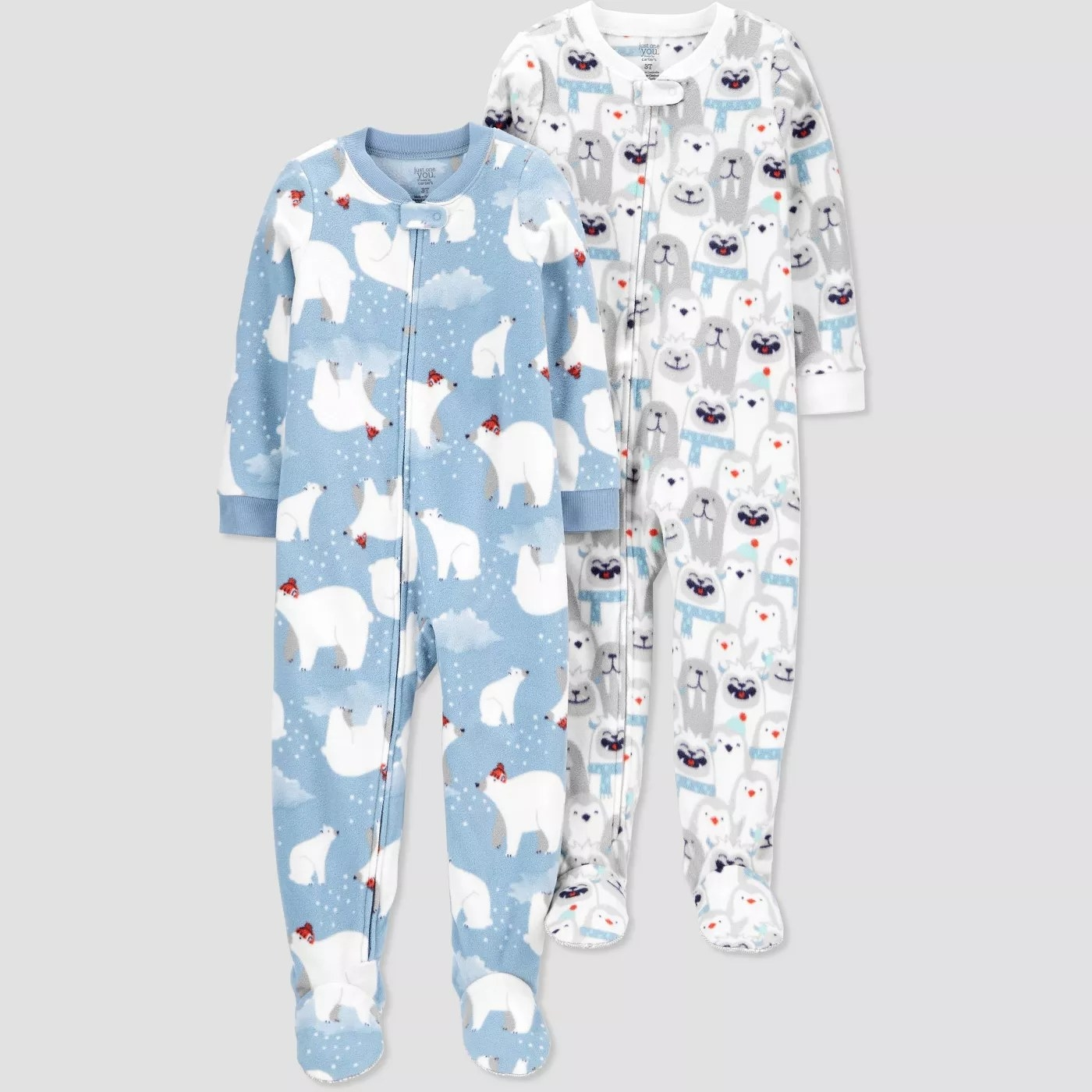 A blue, footed pajama with a polar bear pattern and a white pair with a yeti pattern