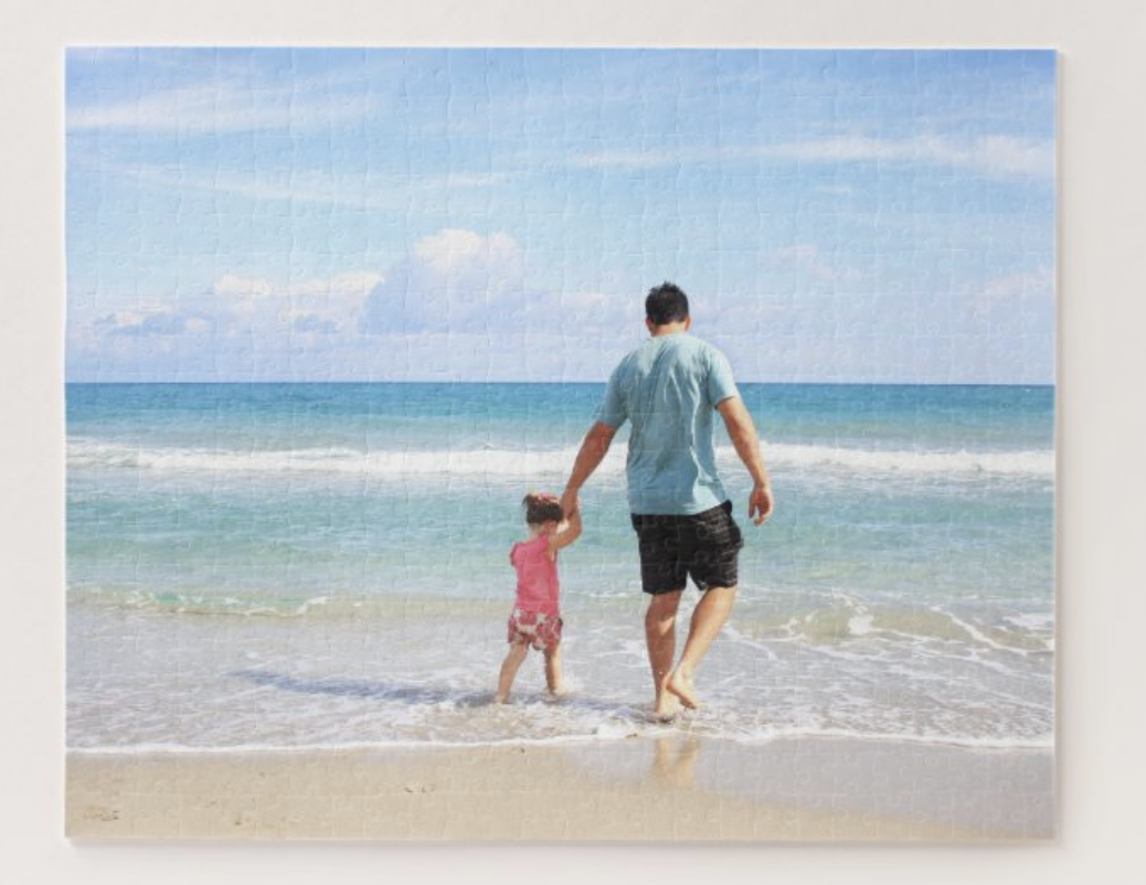 A pic of an adult and child on a beach in puzzle form