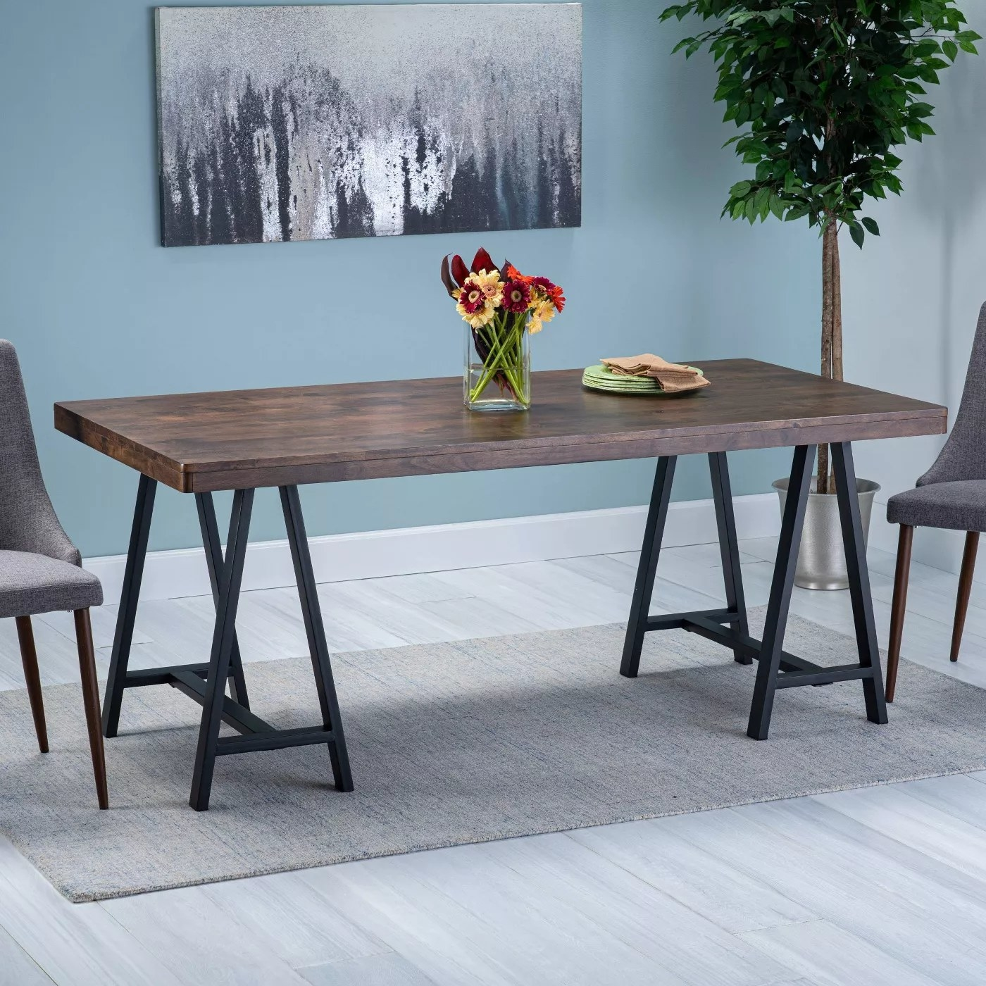 A 70-inch dining table with a walnut countertop and black iron, sawhorse-style legs
