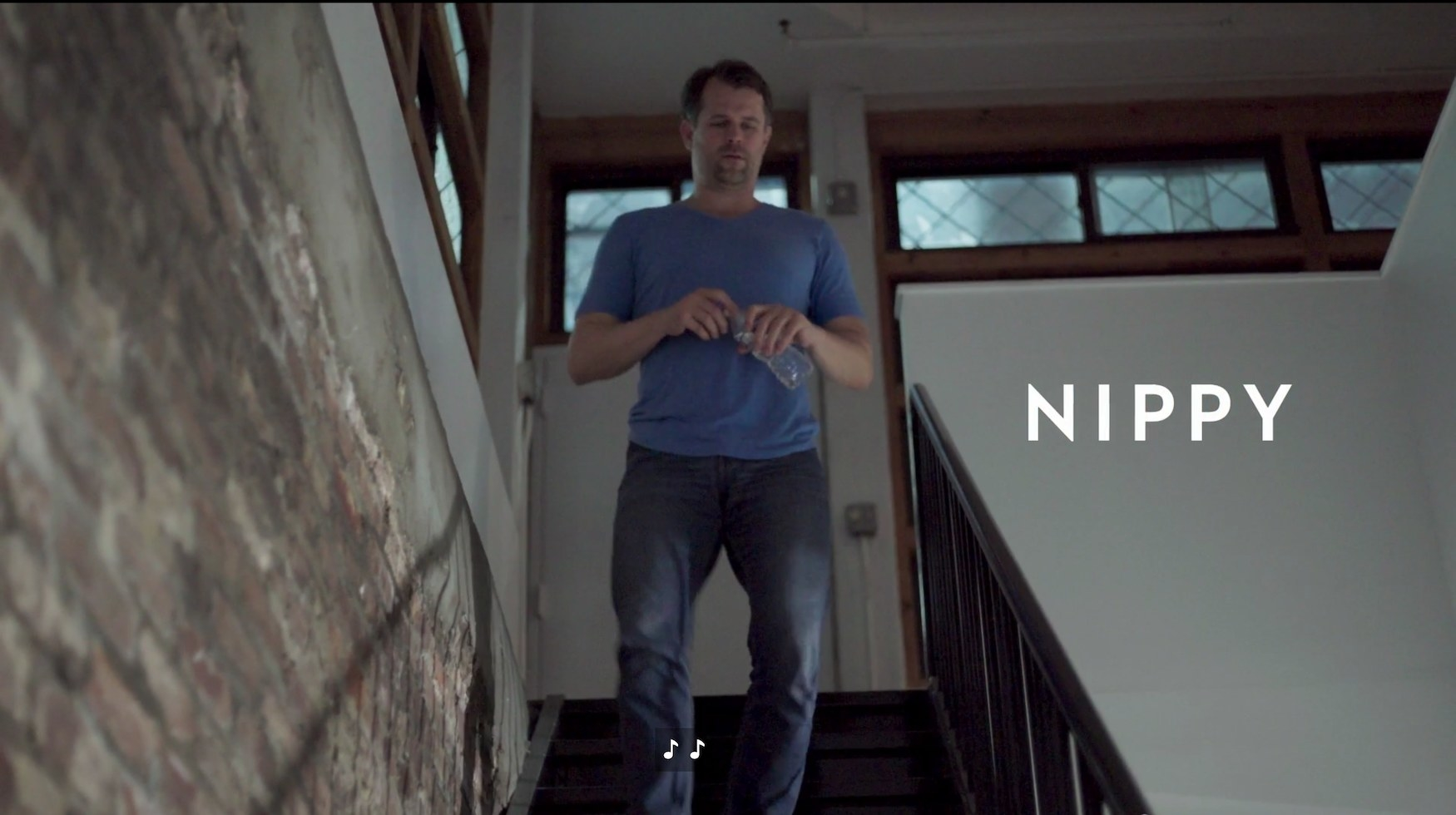 A screenshot of a man in walking downstairs with a title card identifying him as Nippy