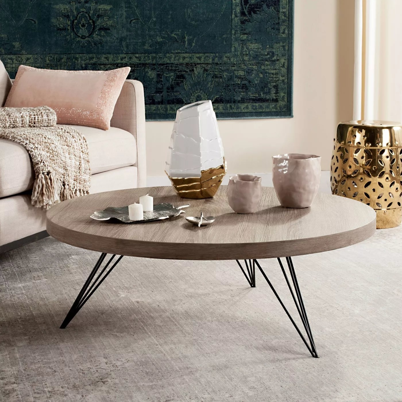 A round, light gray coffee table with black, hairpin legs