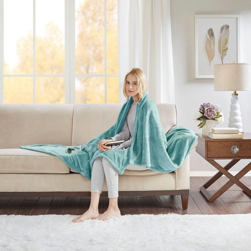 Model sits under the aqua heated blanket
