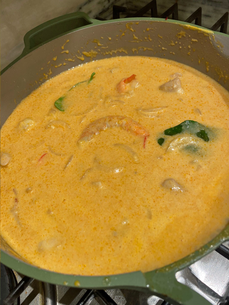 The mango coconut curry sauce simmering in a skillet.