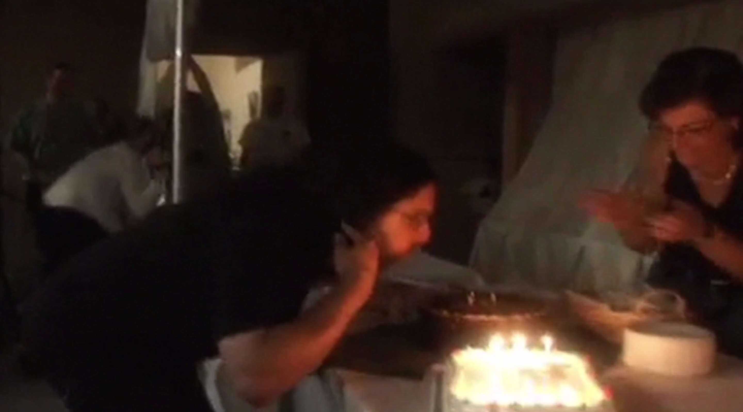 A man and a woman blowing out candles on several cakes