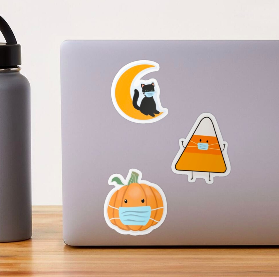 The large size stickers — a black cat on a crescent moon, a pumpkin, and a candy corn, all wearing surgical masks — on a laptop