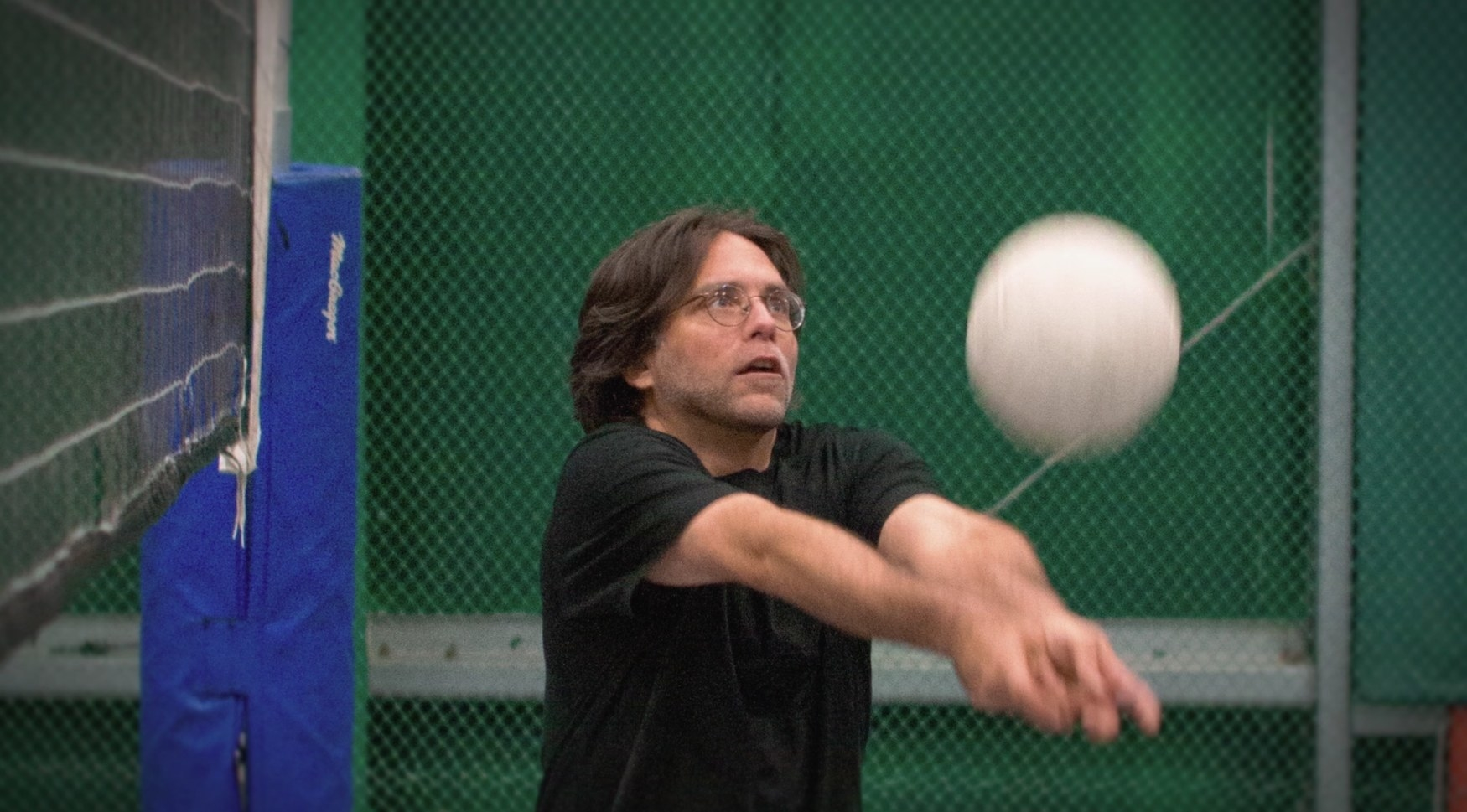 A man in glasses hitting a volleyball