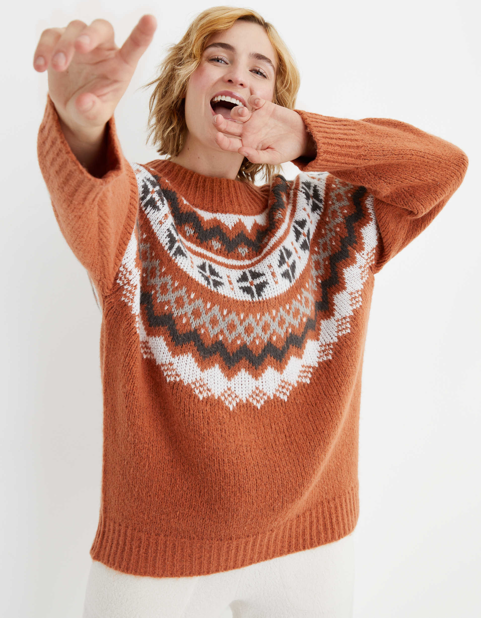 Model wearing the crewneck sweater in orange with a black, white, and grey half-circular geometric pattern around the neckline