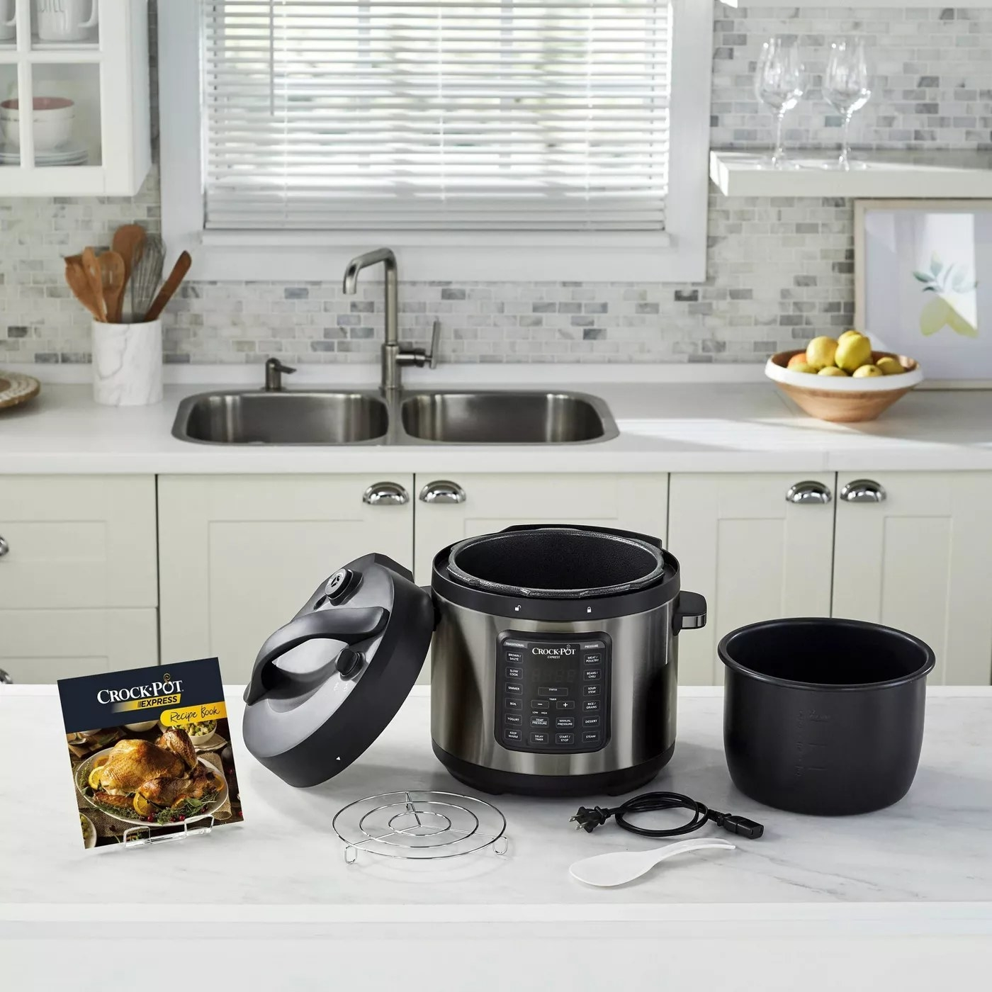 The pressure cooker with the removable cooking pot, steaming rack, serving spoon, and recipe book