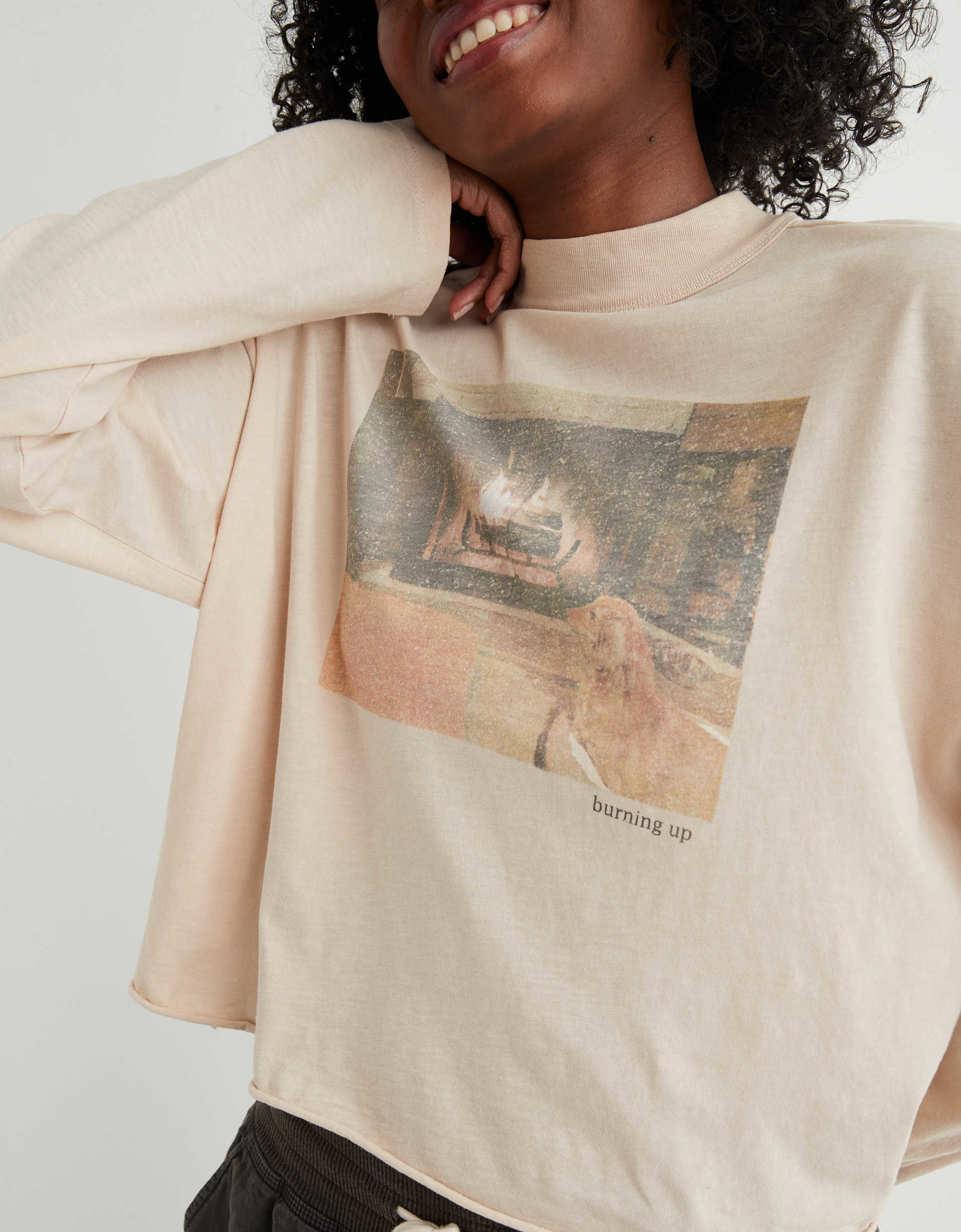 Model wearing the t-shirt in beige with a faded picture of a fireplace and a dog on it