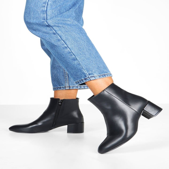 Model wears black block-heel booties with blue jeans