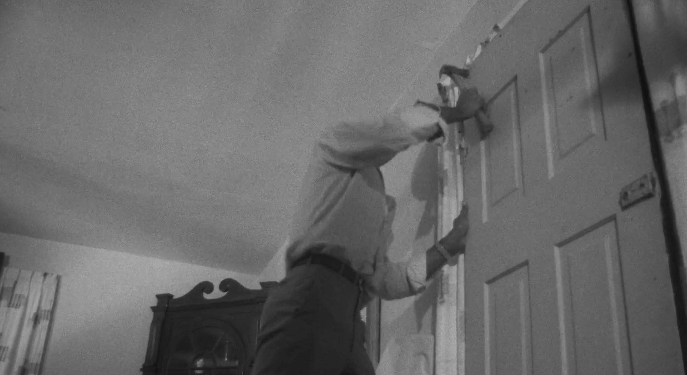A man hammering a door shut