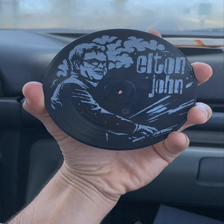 reviewer holding up an Elton John coaster