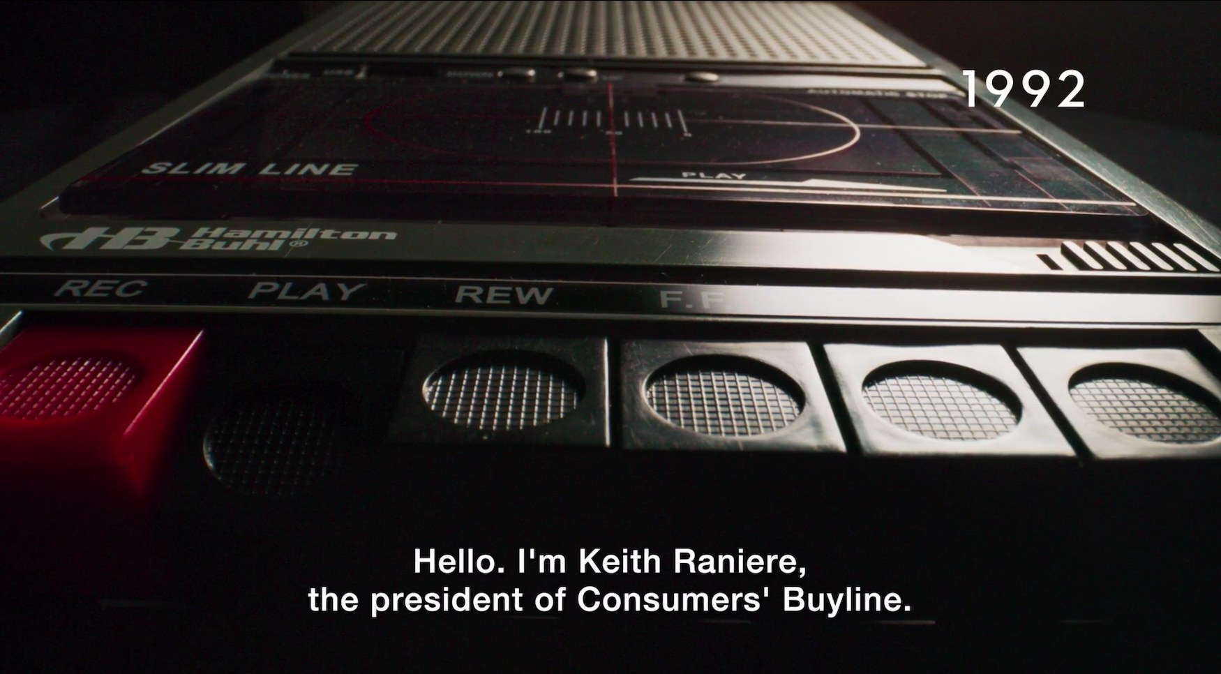 "A tape recorder with the caption text ""Hello, I'm Keith Raniere, the president of Consumers' Buyline"""