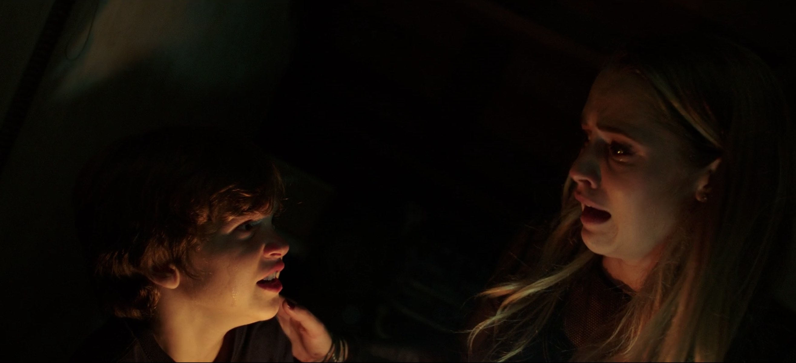 A woman and a little boy staring at each other in the dark with dim lighting