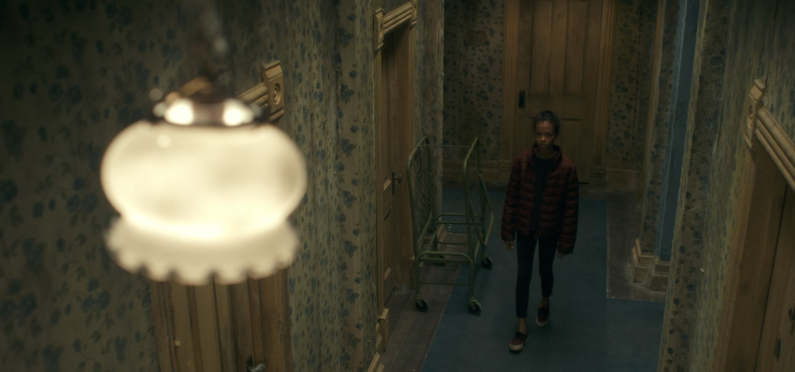 A child standing in a hotel corridor staring at a ceiling light