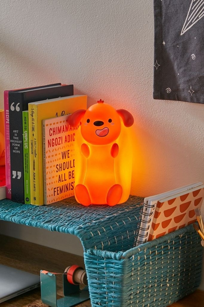 The light, which looks like a vertical hot dog with paws and a dog head in a bun, on a bookshelf. It's about as tall as a paperback book