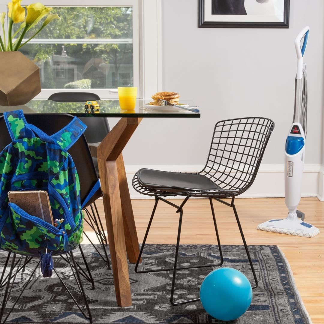 A small steam mop in the corner of a dining room with a large glass table and metal chair