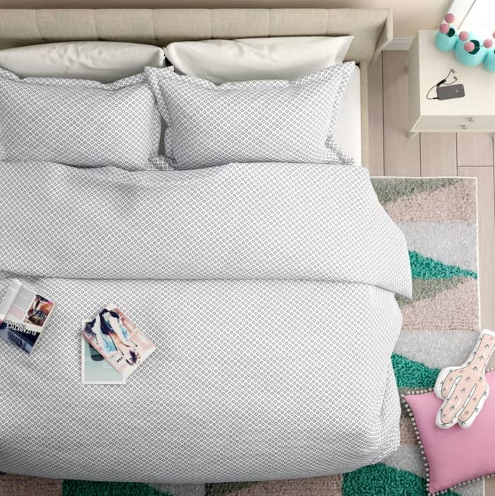 The duvet cover set with two shams in white and blue on a bed