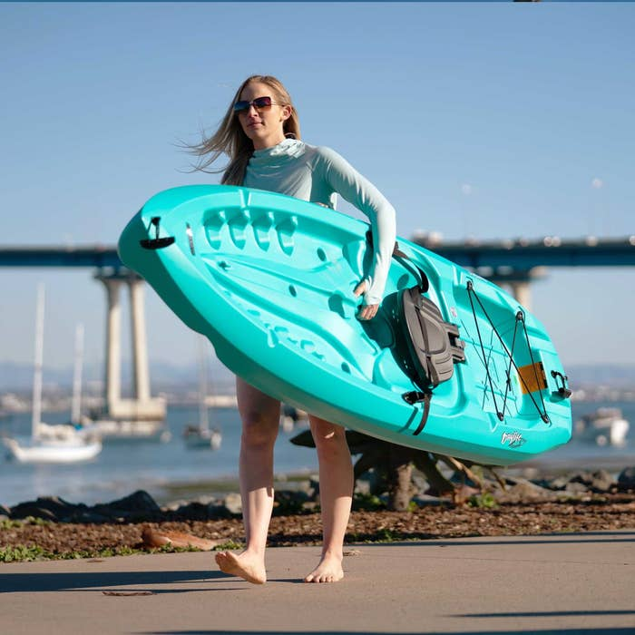 A model carrying a blue kayak in front of the ocean
