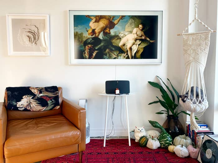 The television with a white frame and a classic painting displayed in the center