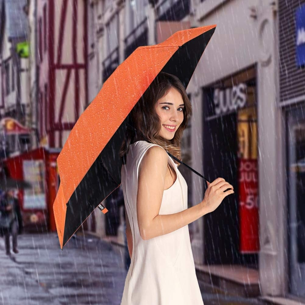 A model carries the Yoobure Small Mini Umbrella open in the rain