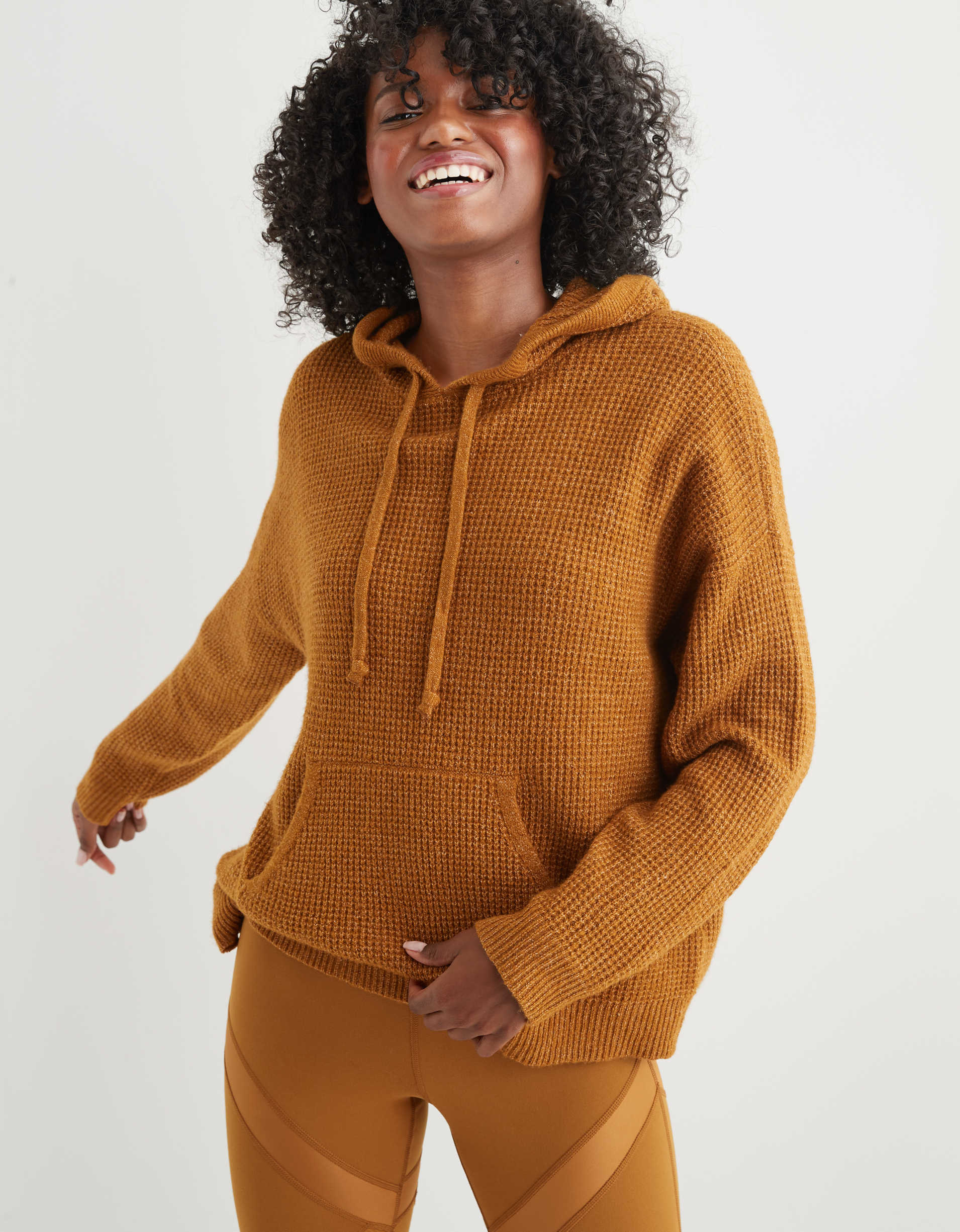Model wearing the hooded sweatshirt with a drawstring and front pocket in mustard yellow