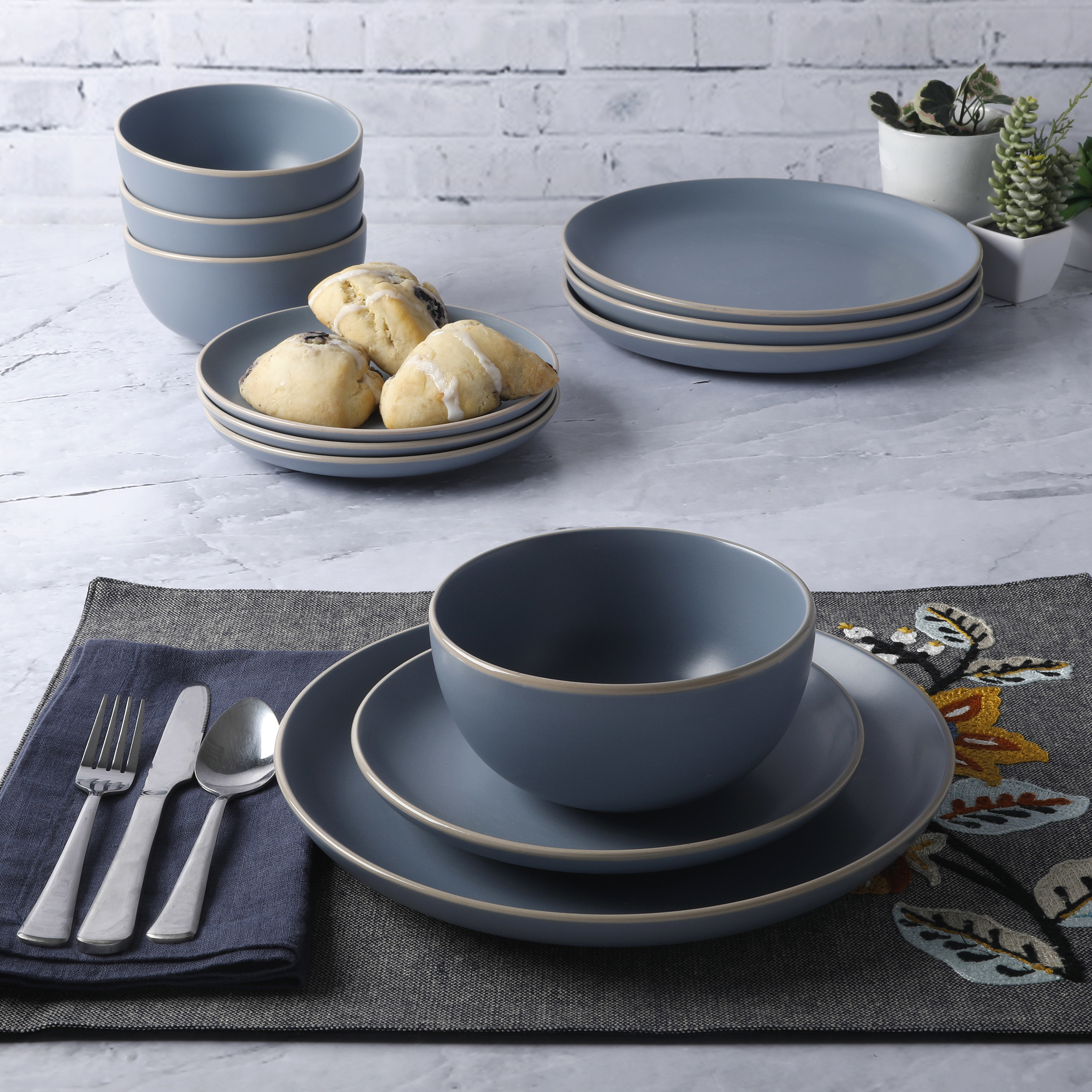 The 12-piece dinnerware set displayed on a place setting to show color and size