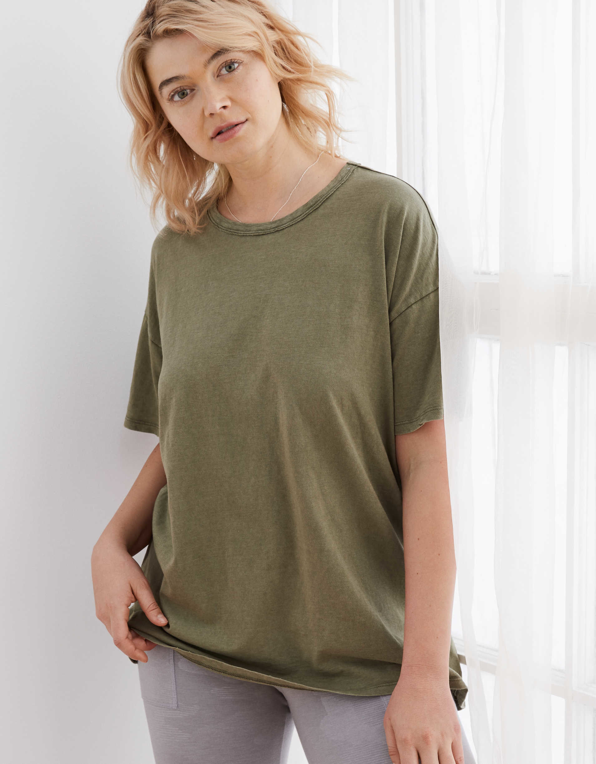 Model wearing the scoop-neck t-shirt with dropped shoulders and a long hem in olive green