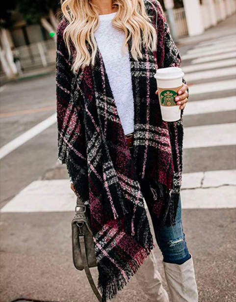 A person wearing the blanket shawl with a pair of knee high boots while holding a coffee