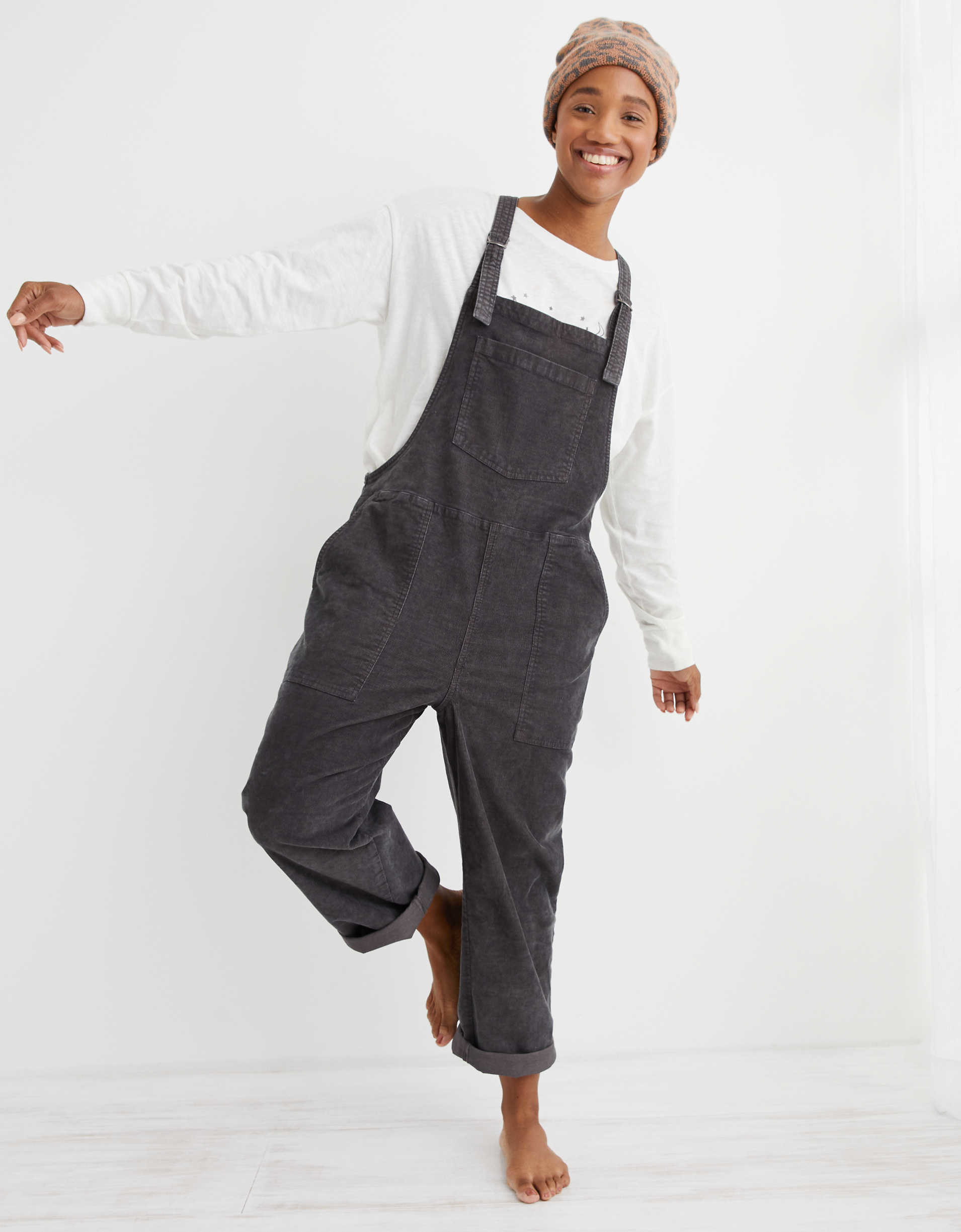 Model wearing the overalls with cuffed hems, oversized pockets, and a large pocket in the top middle in dark grey