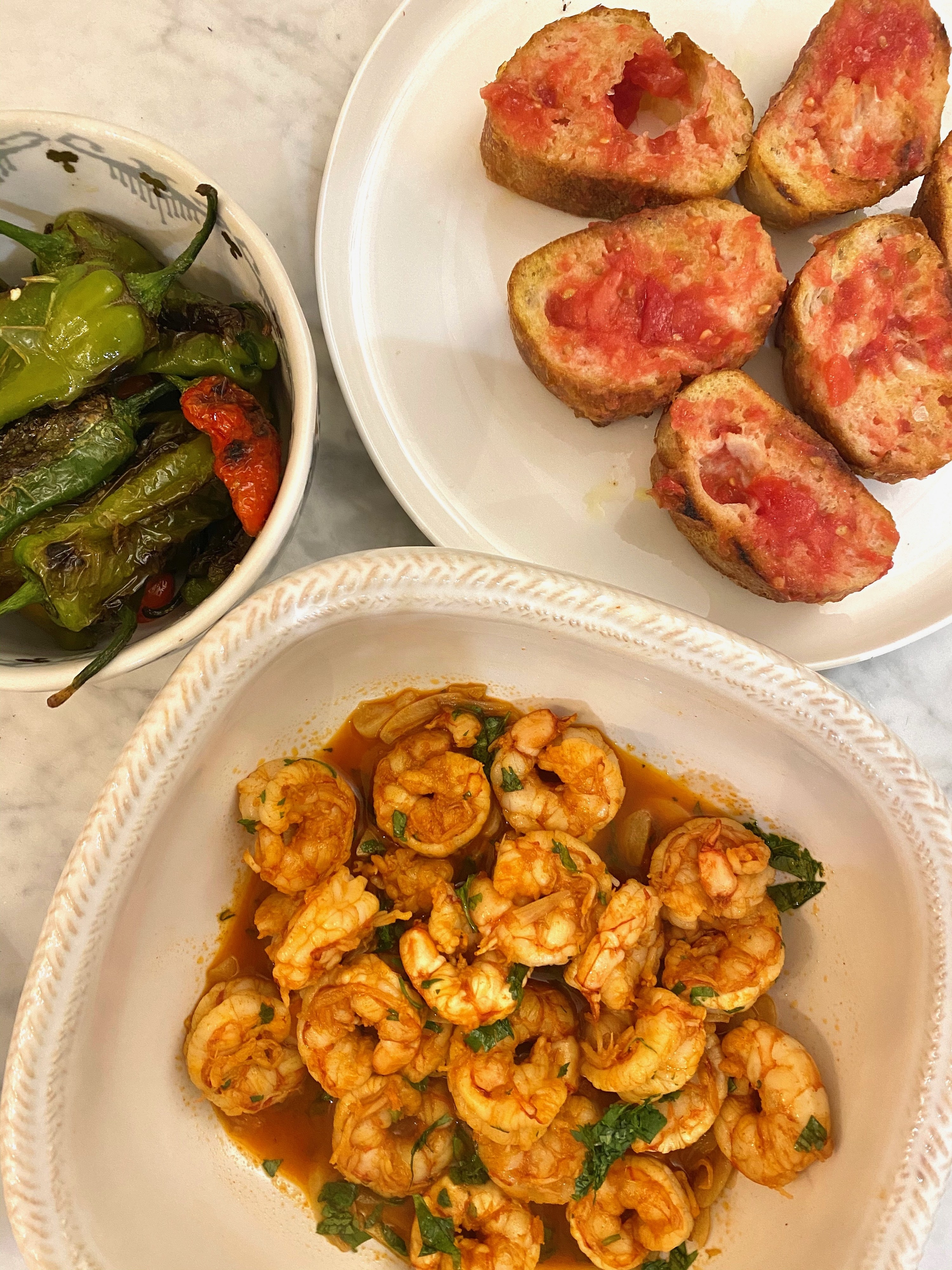 A plate of tomato bread, a bowl of shrimp in garlic sauce, and a third bowl of shishito peppers.