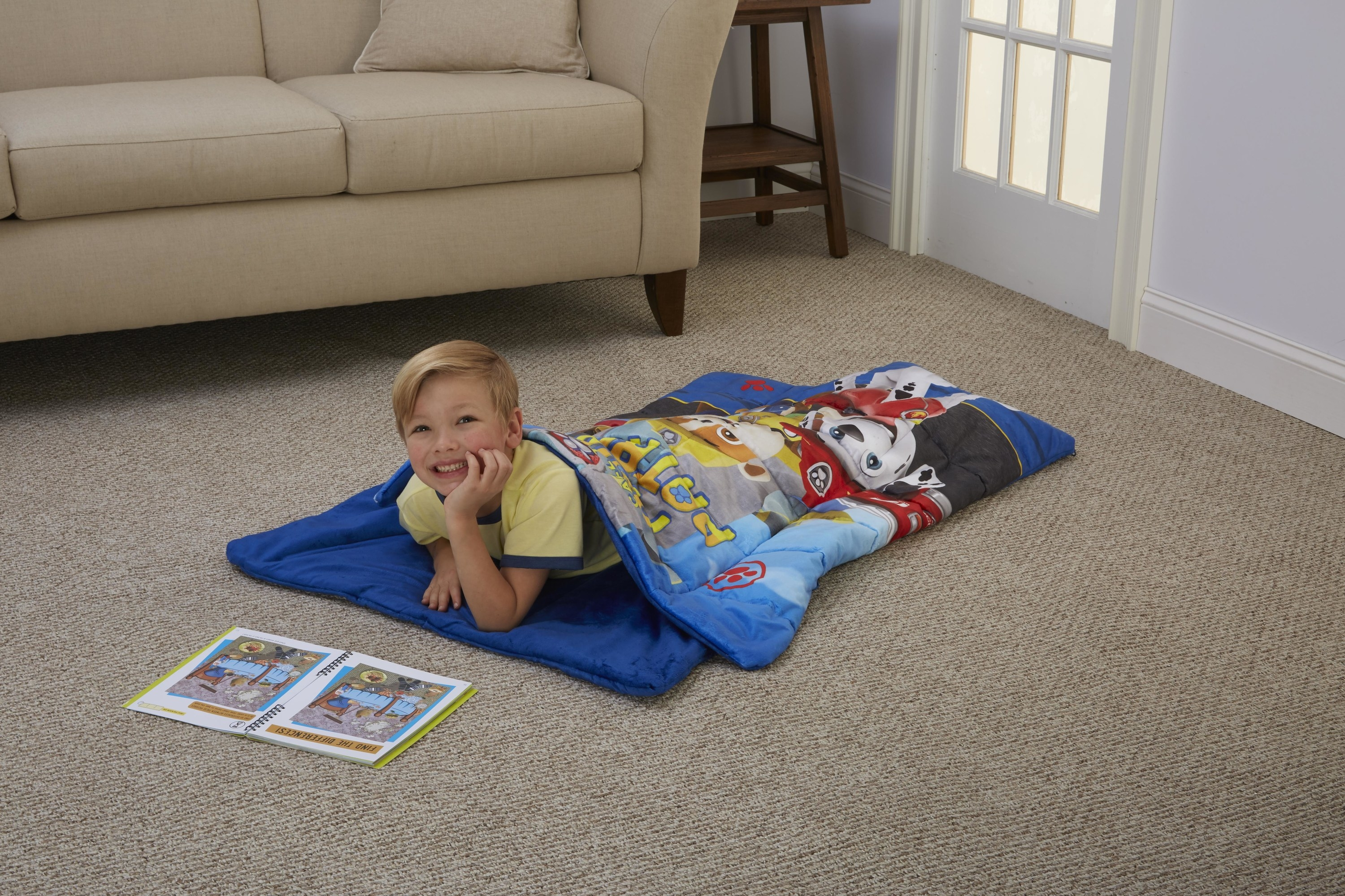A child model laying on the floor in the sleeping bag