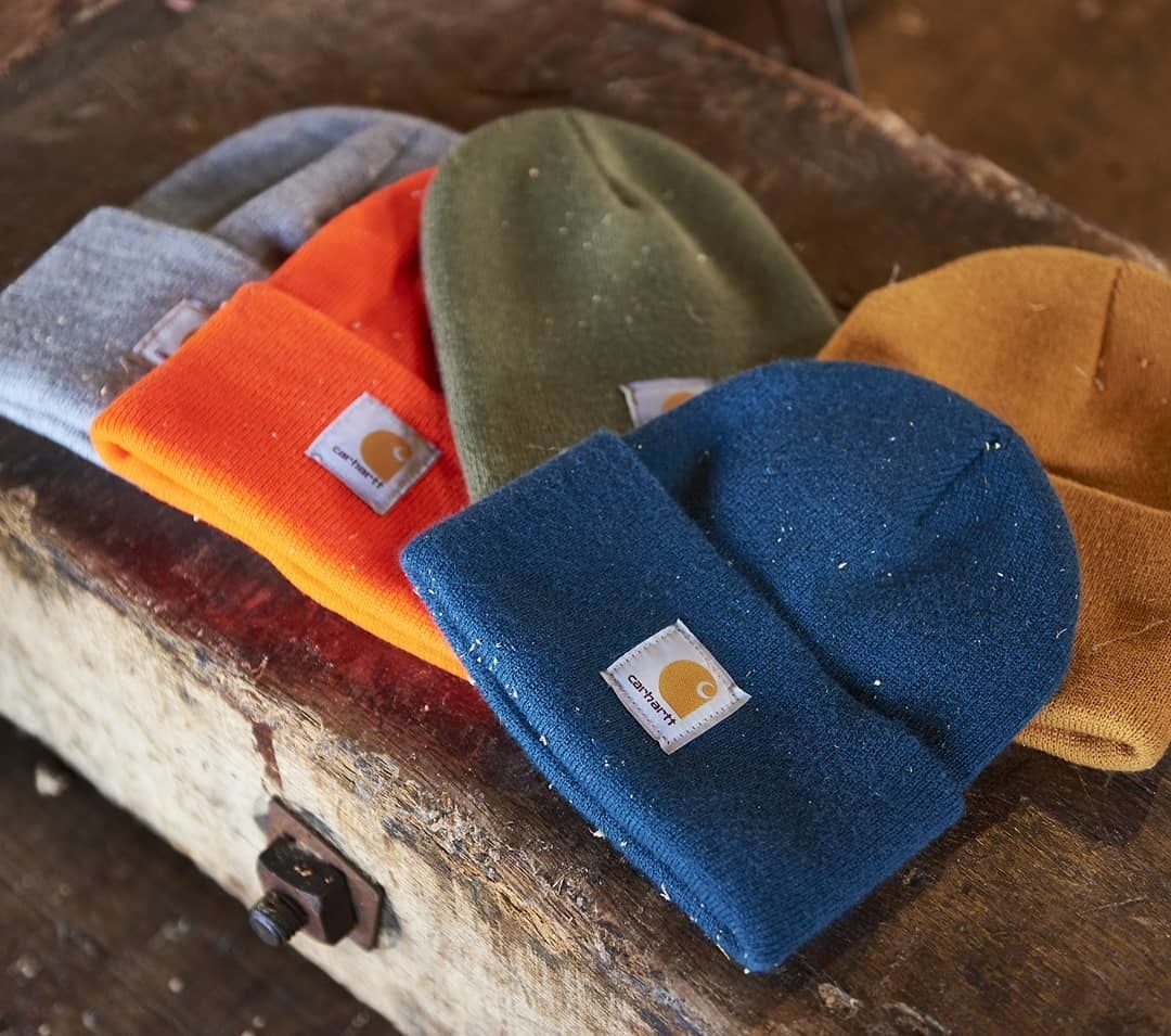 Several Carhartt beanies on a wood bench
