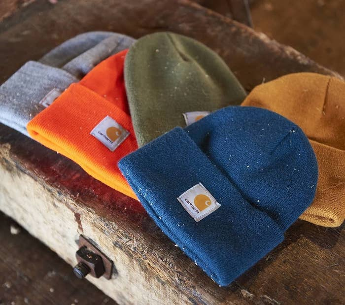 Five beanies on a wooden bench