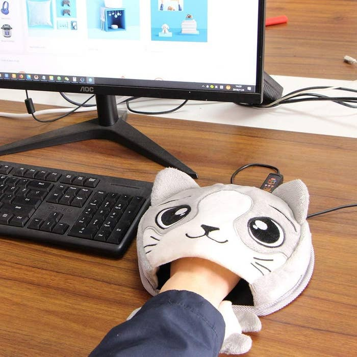 A person with their hand inside the heated mouse pad