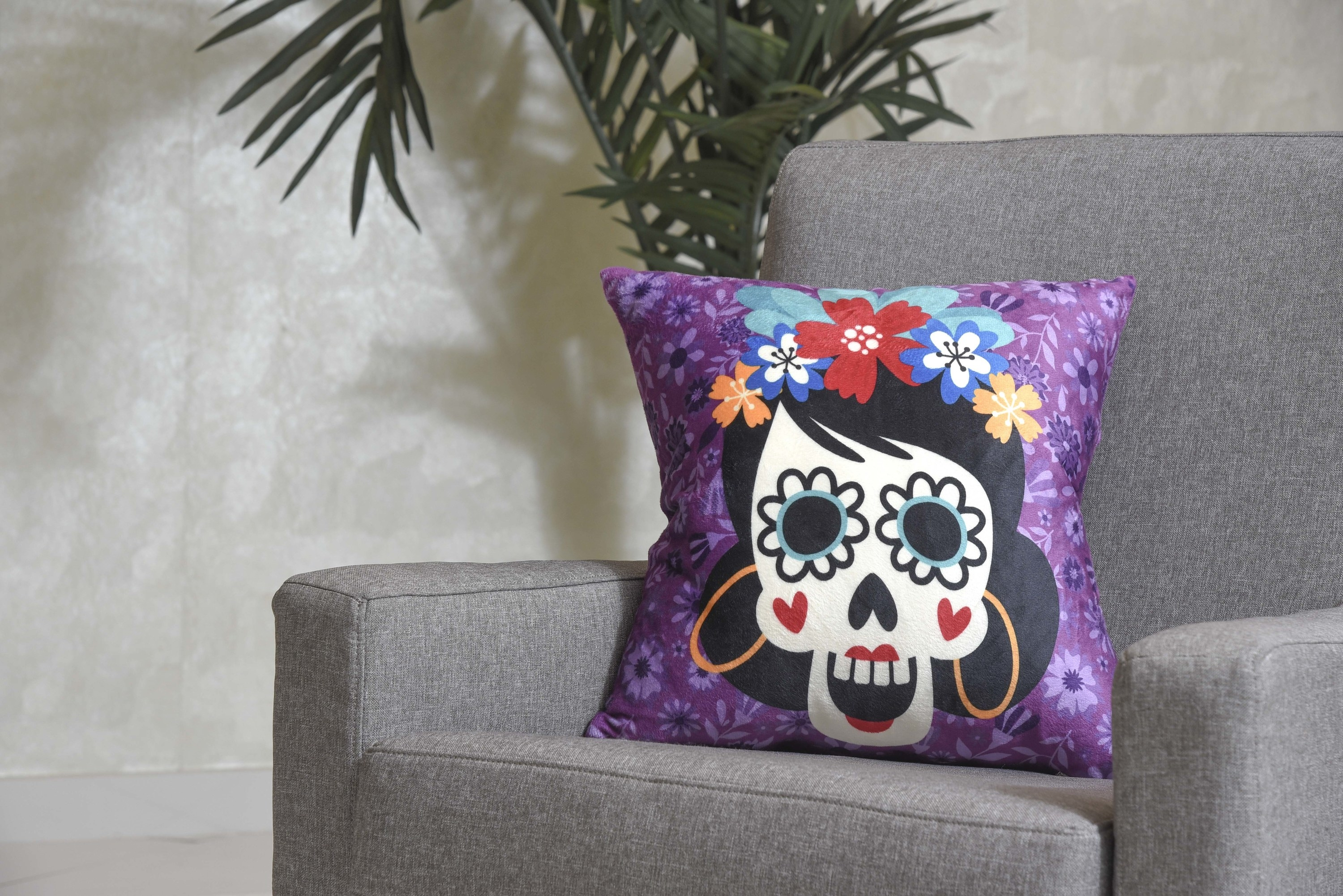 The purple skull printed pillow on a grey couch