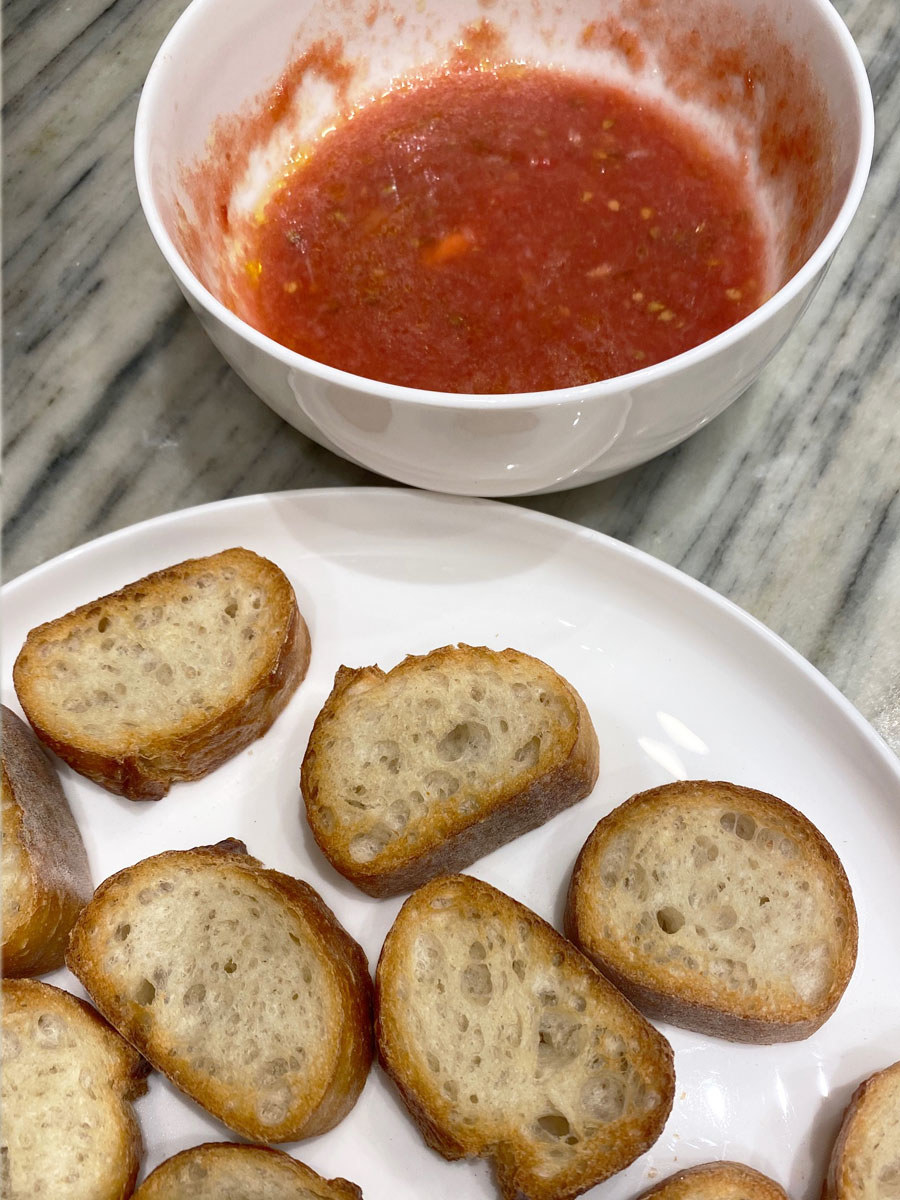 A bowl of tomato sauce and a plate of sliced, toasted bread.
