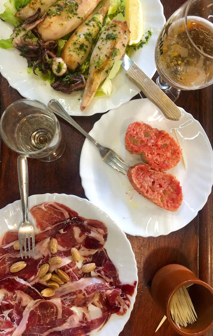 Plates of Spanish tomato bread, jamon iberico, and grilled squid.