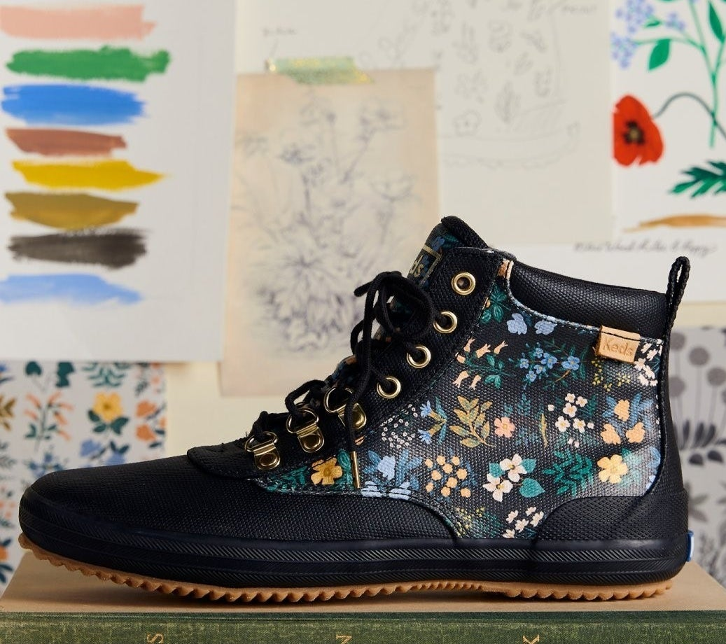 A floral boot ontop of a shoe box