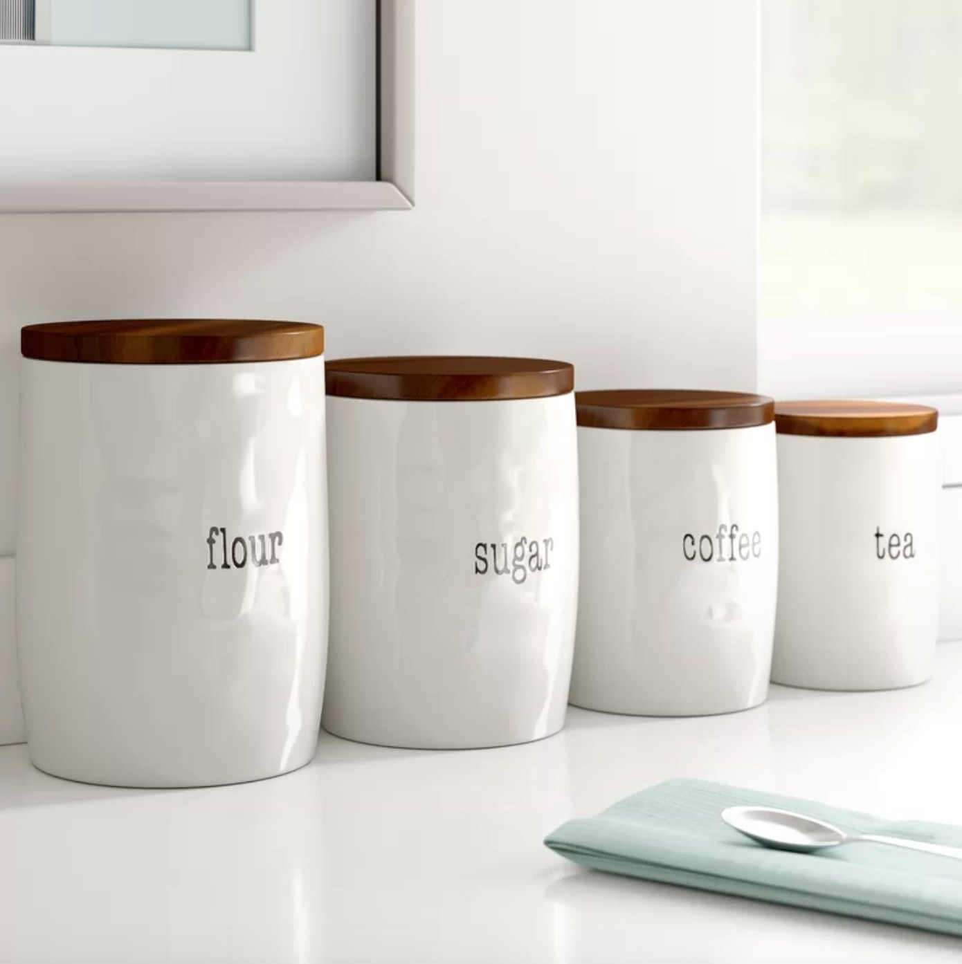 The four-piece kitchen canister in white with dark wood lids