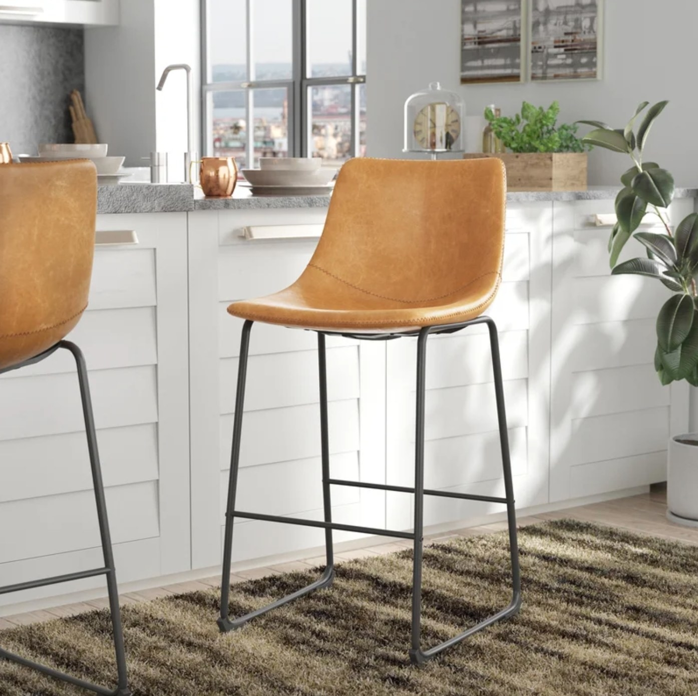 The set of bar stools with black legs and a tan seat