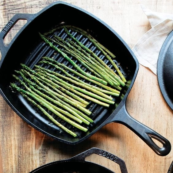 The black cast iron pan with asparagus cooking inside