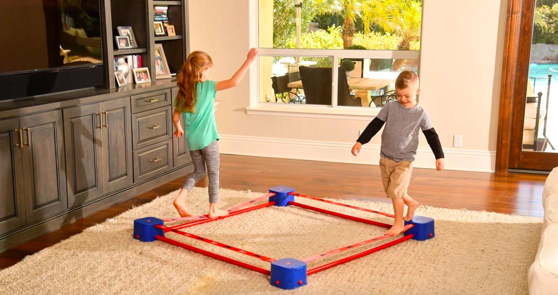 Two children walking across square slack line in living room