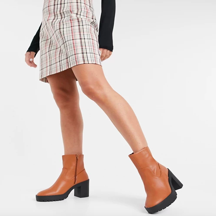 Model wears chunky platform ankle boots in a tan shade with a striped dress