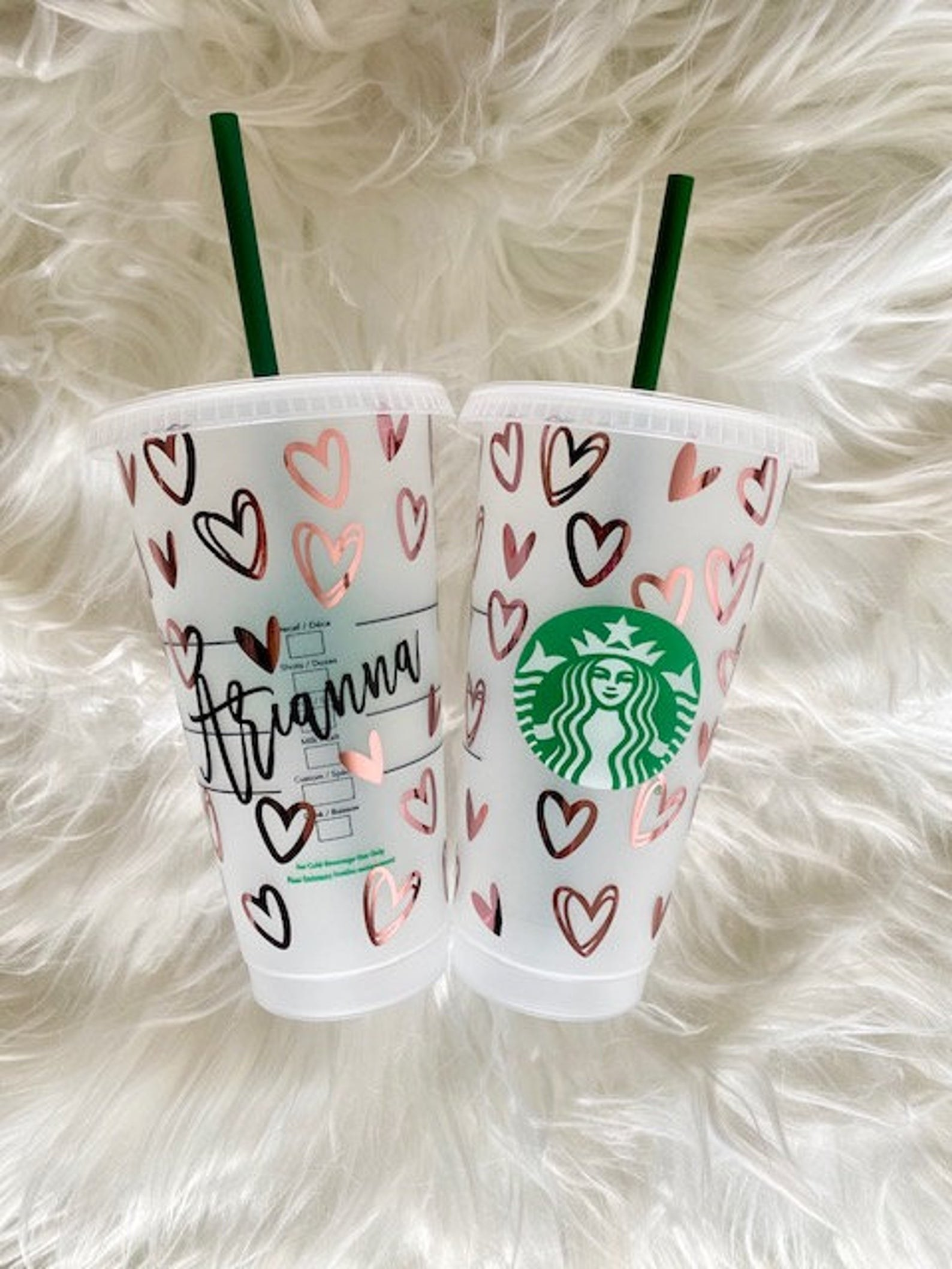A reusable clear Starbucks cup with a straw that has hearts and a name on it