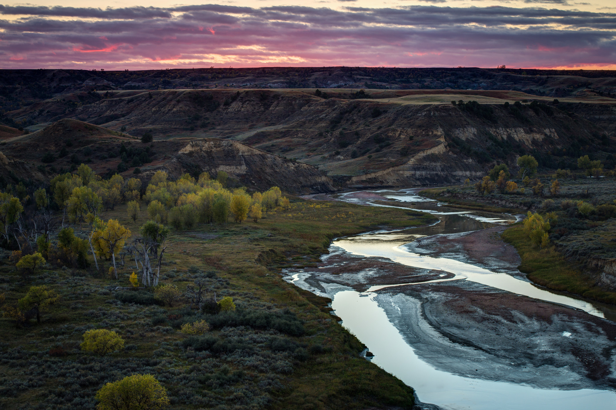 A sunset hovers over a wide shot of greenery, cliffs, and a snaking river