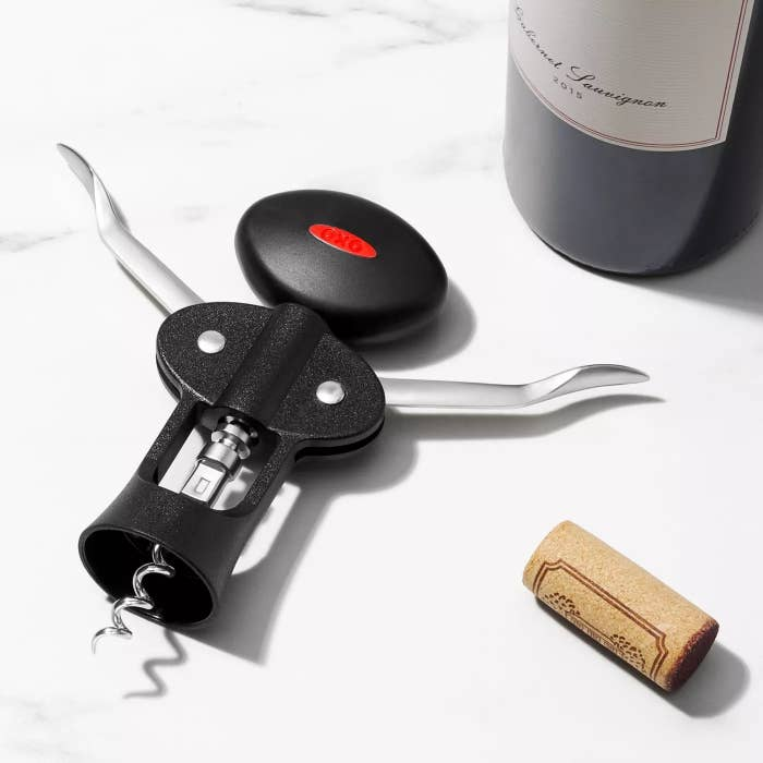 The corkscrew next to a bottle of wine on a countertop